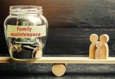 Glaskruik met geld en de woorden 'Familieonderhoud 'en de familie op de schalen Het concept medische verzekering van het leven, stock foto