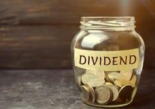 Glaskruik met het woorddividend Een dividend is een betaling door een bedrijf aan zijn aandeelhouders als distributie van winsten stock fotografie