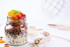 Glaskruik met ingrediënten voor het koken granola op witte achtergrond Havervlokken, honing, noten, gedroogd fruit en zaden royalty-vrije stock foto