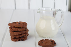 Glaskruik met melk en chocoladeschilferkoekjes Stock Foto
