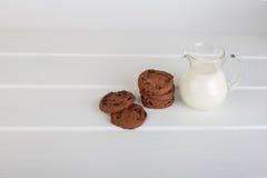 Glaskruik met melk en chocoladeschilferkoekjes Stock Afbeelding