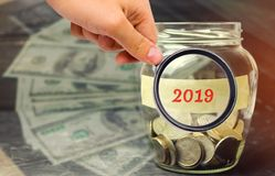 Glaskruik met muntstukken en de inschrijving '2019 ' Financiële begroting planning Investeringen en plannen voor het nieuwe jaar  stock foto's