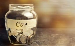 Glaskruik met muntstukken en de inschrijving 'Auto ' Het concept accumulatie van geld voor een auto Besparingsgeld voor een droom royalty-vrije stock afbeeldingen