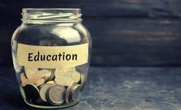 Glaskruik met muntstukken en de inschrijving 'Onderwijs ' Het concept onderwijs voor zich of kinderen Accumulatie van geld voor royalty-vrije stock fotografie