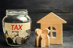 Glaskruik met muntstukken en de inschrijvings` belasting ` en een plattelandshuisje Belastingen op onroerende goederen, betaling  stock foto's