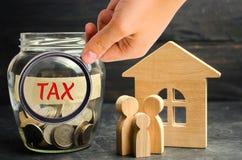 Glaskruik met muntstukken en de inschrijvings` belasting ` en een plattelandshuisje Belastingen op onroerende goederen, betaling  royalty-vrije stock foto