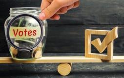 Glaskruik met muntstukken en de woorden 'de Stemmen en checkbox op de schalen Concept stemming voor geld Het omkopen van kiezers  stock foto