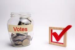 Glaskruik met muntstukken en de woordenstemmen en checkbox Concept stemming voor geld Het omkopen van kiezers Corruptie in kies royalty-vrije stock foto