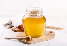 Glaskruik van honing en houten dipper op wit stock foto's