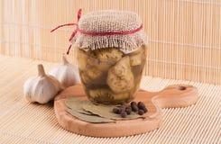 Glaskruik van ingeblikte aubergine, knoflook, laurierblad en pepererwten Royalty-vrije Stock Foto's