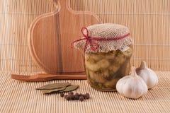 Glaskruik van ingeblikte aubergine, knoflook, laurierblad en pepererwten Royalty-vrije Stock Foto