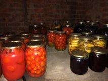 Glaskruiken met komkommers, tomaten en jam in de kelder stock foto