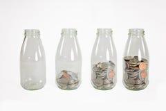 Glaskruiken met muntstukken zoals geïsoleerd diagram, - besparingenconcept Stock Foto's