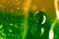 Glaskugel auf einem Glastisch mit Reflexion auf grünem gelbem Hintergrund Schönes bokeh Kunstwerk Lizenzfreies Stockfoto