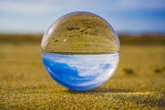 Glaskugel, die im Sand vor dem hintergrund der Meereswellen und im Himmel mit Wolken liegt lizenzfreie stockbilder