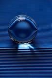 Glaskugel oder Wassertropfen auf einem Hintergrund der blauen Wellpappe Säubern Sie und glänzen Sie Lizenzfreie Stockbilder