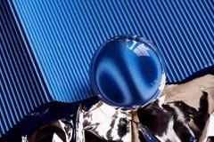 Glaskugel oder Wassertropfen auf einem Hintergrund der blauen Wellpappe und der Folie Säubern Sie und glänzen Sie Lizenzfreie Stockbilder