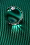 Glaskugel oder Wassertropfen auf einem Hintergrund der grünen Wellpappe Säubern Sie und glänzen Sie Lizenzfreies Stockbild