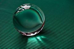 Glaskugel oder Wassertropfen auf einem Hintergrund der grünen Wellpappe Säubern Sie und glänzen Sie Stockbild