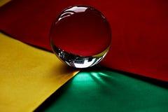 Glaskugel oder Wassertropfen auf einem Hintergrund des gelben, roten und grünen Samtpapiers Säubern Sie und glänzen Sie Lizenzfreies Stockfoto