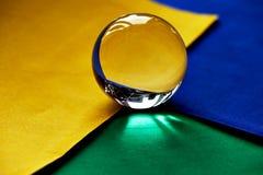 Glaskugel oder Wassertropfen auf einem Hintergrund des grünen, gelben und blauen Samtpapiers Säubern Sie und glänzen Sie Stockbilder