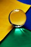 Glaskugel oder Wassertropfen auf einem Hintergrund des grünen, gelben und blauen Samtpapiers Säubern Sie und glänzen Sie Stockfotos