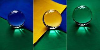 Glaskugel oder Wassertropfen auf einem Hintergrund des grünen, gelben und blauen Samtpapiers Säubern Sie und glänzen Sie, Collage Stockbilder