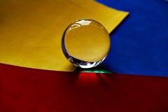 Glaskugel oder Wassertropfen auf einem Hintergrund des grünen, roten und blauen Samtpapiers Säubern Sie und glänzen Sie Lizenzfreie Stockfotografie