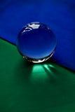 Glaskugel oder Wassertropfen auf einem Hintergrund des grünen und blauen Samtpapiers Säubern Sie und glänzen Sie Stockbilder