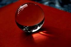 Glaskugel oder Wassertropfen auf einem Hintergrund des roten Samtpapiers Säubern Sie und glänzen Sie Lizenzfreie Stockfotografie