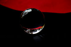Glaskugel oder Wassertropfen auf einem Hintergrund des roten und schwarzen Samtpapiers Säubern Sie und glänzen Sie Lizenzfreie Stockbilder