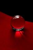 Glaskugel oder Wassertropfen auf einem Hintergrund des roten und schwarzen Samtpapiers Säubern Sie und glänzen Sie Stockbild