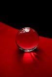 Glaskugel oder Wassertropfen auf einem Hintergrund des roten und schwarzen Samtpapiers Säubern Sie und glänzen Sie Stockfotografie