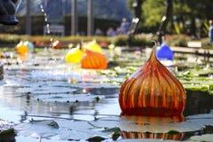 Glaskunst die in lelievijver drijven Stock Afbeeldingen