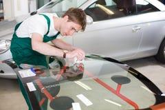 Glasmästare med bilvindrutan som göras av exponeringsglas Arkivbild