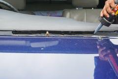 Glasmästare som använder hjälpmedel som reparerar för att fixa den brutna vindrutan för spricka, wi arkivbild