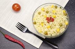 Glasplaat van noedels, vork, Spaanse peper en tomaat stock afbeelding