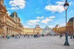 Glaspyramide und das Louvremuseum mit Leutetouristen E Lizenzfreie Stockfotos