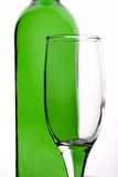 Glass. Transparent glass on a background of green bottles Stock Photography