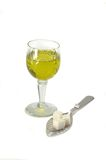 Glass with absinth and spoon with sugar pieces Royalty Free Stock Photo
