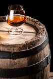 Glass of aged cognac and old wooden barrel. Isolated on a black background Royalty Free Stock Image