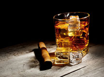 Glass of aged whiskey with cigar and ice cubes Royalty Free Stock Photos