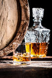 Glass of aged whisky with ice and carafe Stock Images