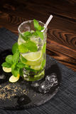 A glass of alcohol beverage from juicy lime, rum, fresh mint and crushed ice on a dark wooden background. Summer mojito, top view. Stock Photo