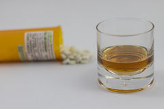 A glass of alcohol and a bottle of Pharmaceuticals Stock Photo