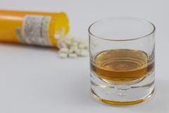 A glass of alcohol and a bottle of pills. One glass of alcohol and one bottles of Pills Royalty Free Stock Image