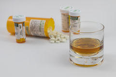 A glass of alcohol and bottles of Pharmaceuticals Royalty Free Stock Photo