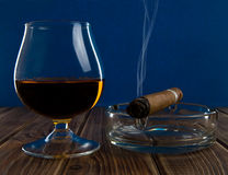 Glass with an alcohol and cigar Stock Photography