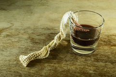 A glass of alcohol and a cloth. Glass of alcohol and a white dirty cloth as a weapon Stock Photography