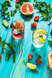 Glass of alcohol cold coctail decorated with ice, fruit and mint staying on wood table. Fresh juice on background with Royalty Free Stock Photos